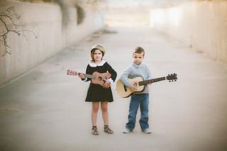 Niños. Niña y niño tocando la guitarra