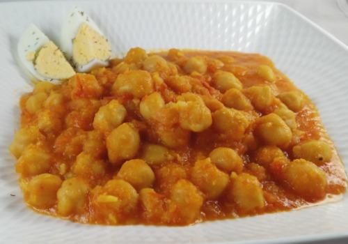 Unos garbanzos con salsa de tomate y adornados con huevo