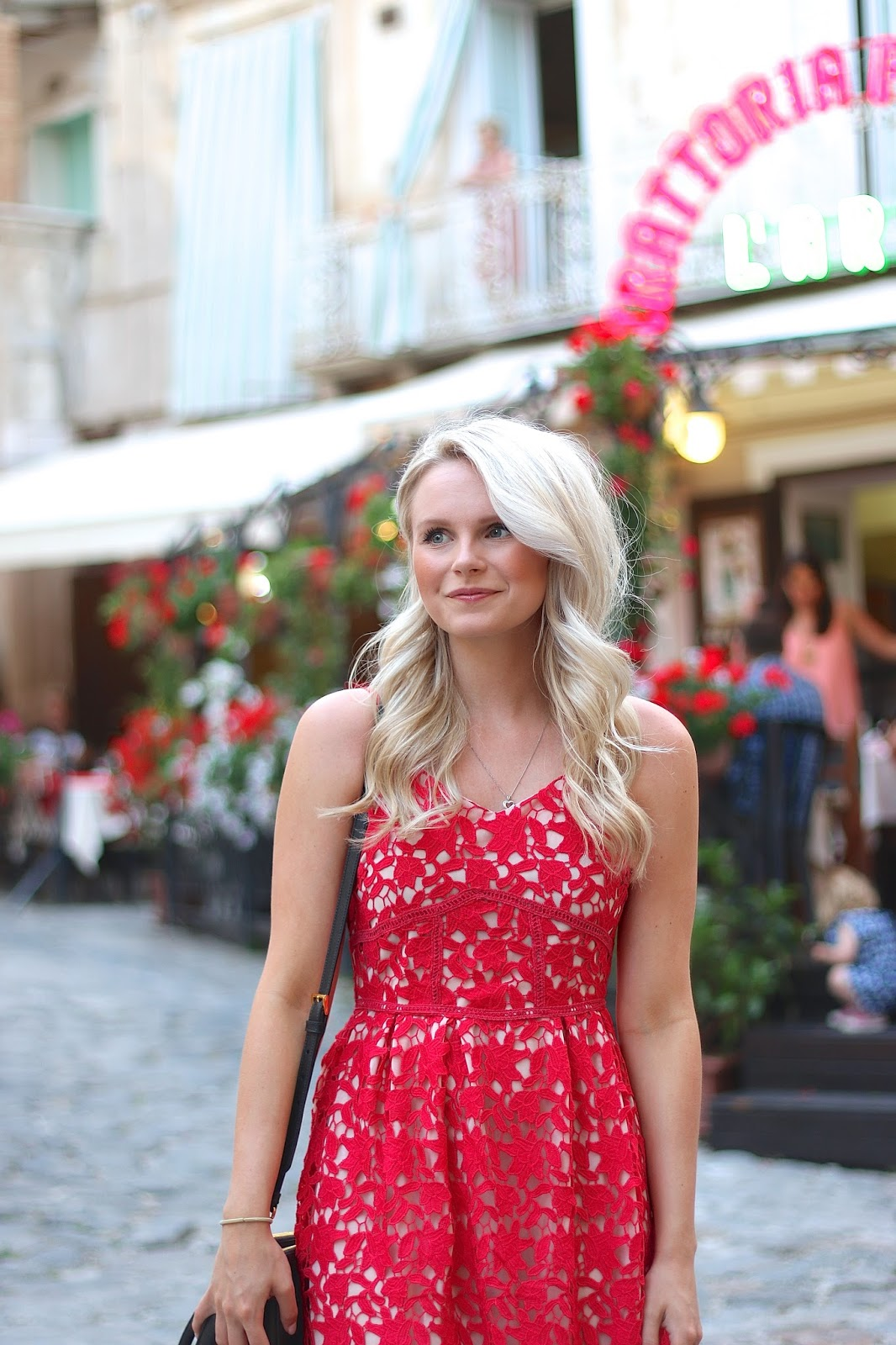 a girl wanders through italy in a red dress