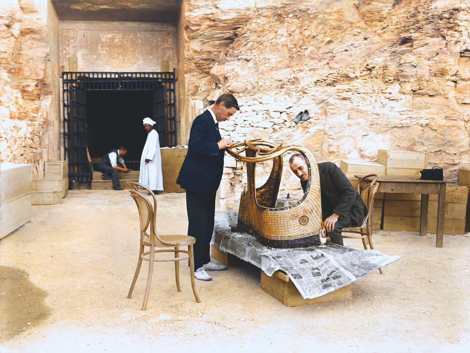 Arthur Mace and Alfred Lucas work on a golden chariot from Tutankhamun's tomb outside the