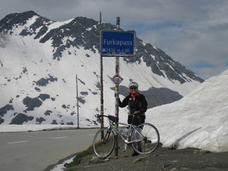 pep and bicycle at the summit of the Furkapass, alongside snow banks, Switzerland