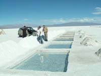 Personas observando desierto de sal con zonas de agua