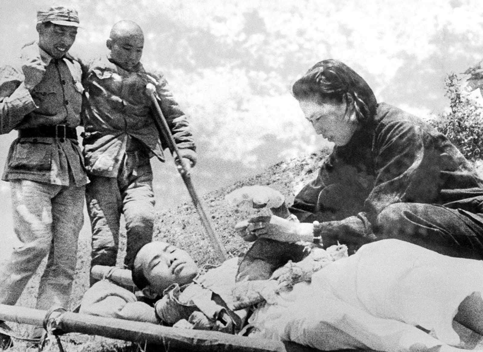 A nurse wraps a bandage around the hand of a Chinese soldier as another wounded soldier limps up for first aid treatment during fighting on the Salween River front in Yunnan Province, China, on June 22, 1943.