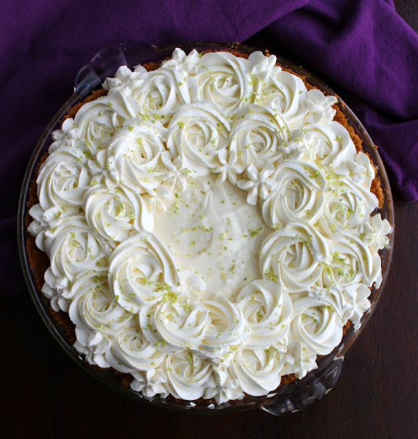 whole key lime pie with whipped cream rosettes and flowers on top