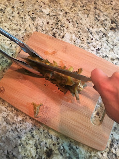 Photo of author holding cooked Brussels stalks on a bamboo cutting board with tongs and splitting them lengthwise with a chef's knife. https://trimazing.com/