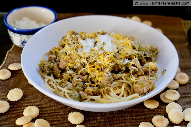 photo of a bowl of chorizo and green tomato chili atop spaghetti noodles