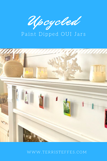 Upcycled paint dipped Oui jars on a fireplace mantle.