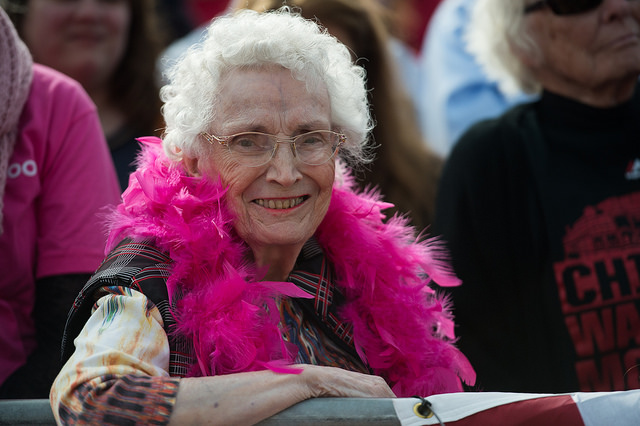 image of an elderly woman who appears to be white at a Hillary Clinton campaign event, leaning against a railing, wearing a pink boa, and smiling