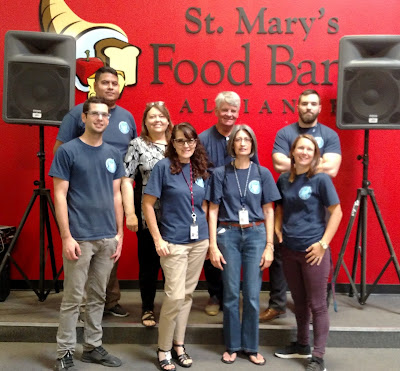 Group shot of Thomas team standing in front of St. Mary's Food Bank wall.
