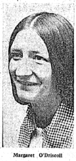 Head and shoulders of a smiling woman with long dark hair, wearing a checked blouse