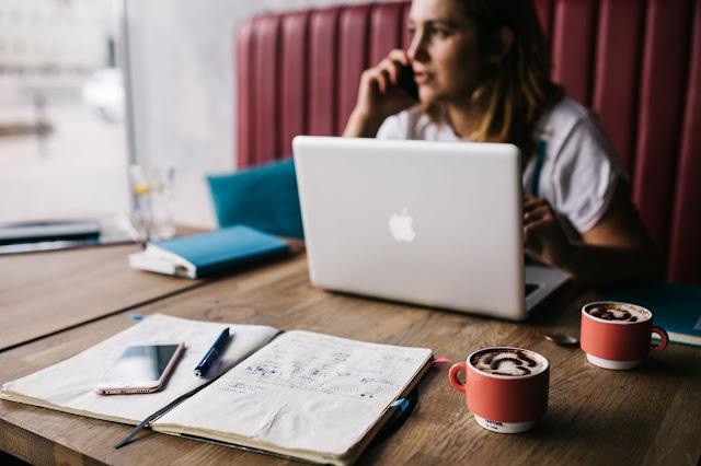 Uma mulher jovem a trabalhar numa mesa de café
