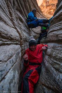 ladies in dry suits climbing through slot canyon Matkatimiba grand canyon of the colorado