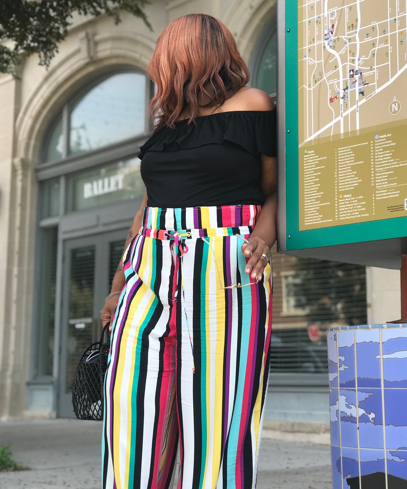 Image: Woman leaning and showing off her fun and quirky stripe pants from New York and Company. Seen first on Bits and Babbles Blog