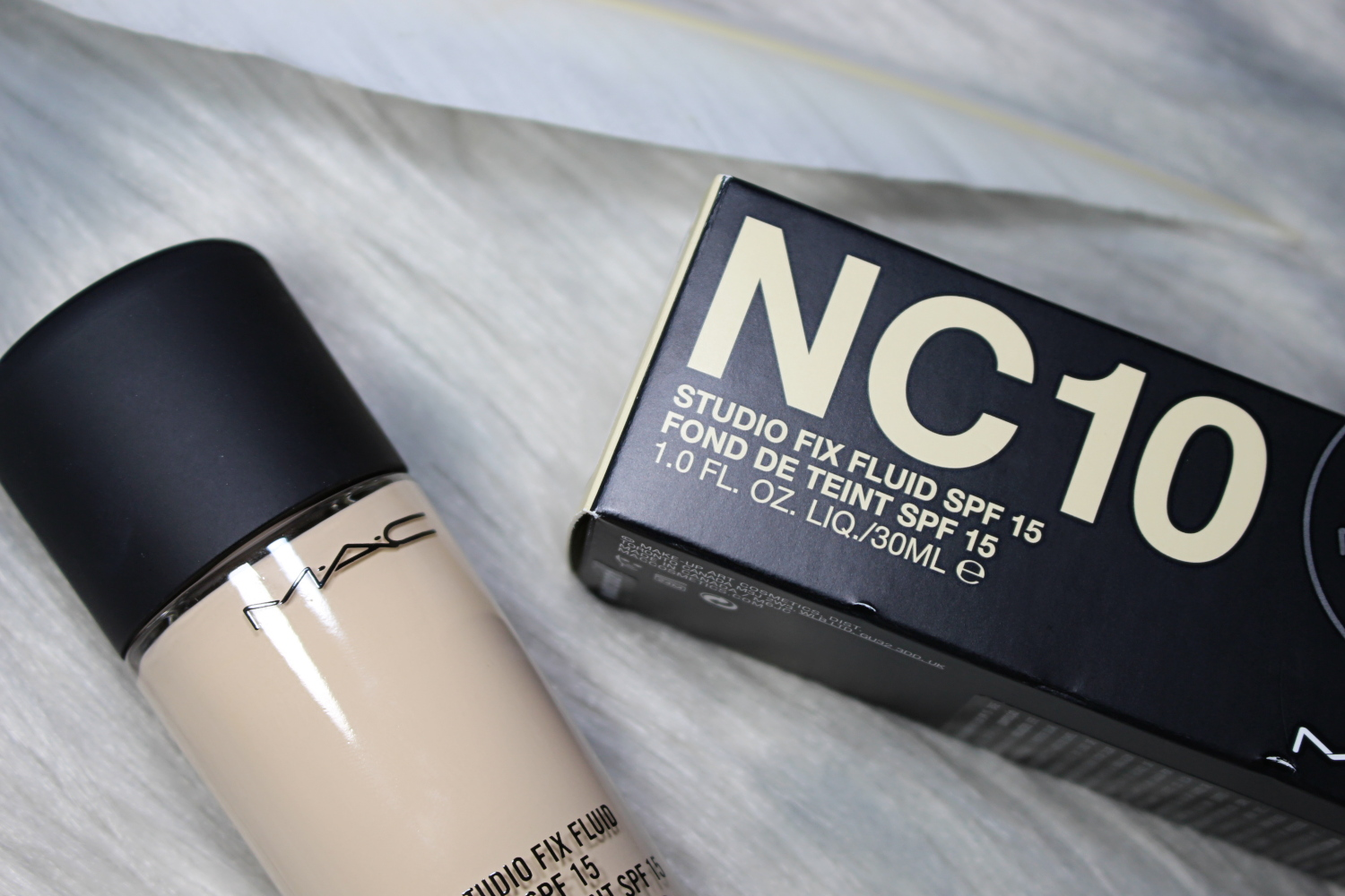 a bottle of mac cosmetics Mac Cosmetics Studio Fix Fluid Foundation In Shade NC 10  is laying on a gray fur