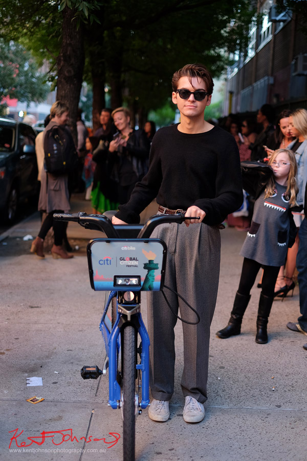Man in black light weight sweater and 80s style full pleated trouses walks a Citi bike along Norfolk Street NYC. Street Fashion Sydney - New York Edition photographed by Kent Johnson