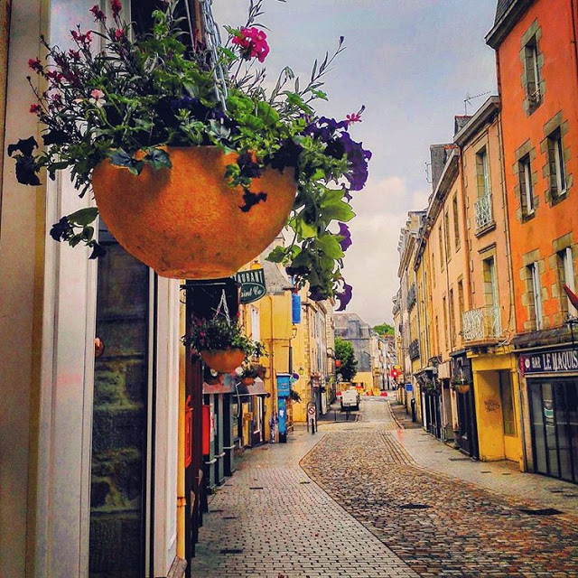A Flowers basket is hanging in city center of Quimper during day time