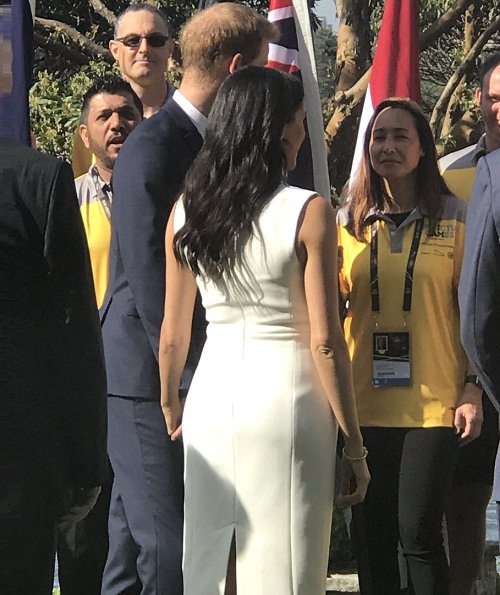 Meghan Markle wore a white Blessed dress by Australian designer Karen Gee, and she wore ​Stuart Weitzman suede pump in Haze Beige