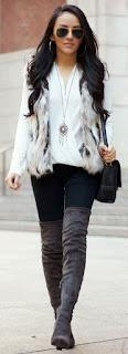 Botas cinza, calças skinny pretas, camisola branca e colete de pêlo cinza