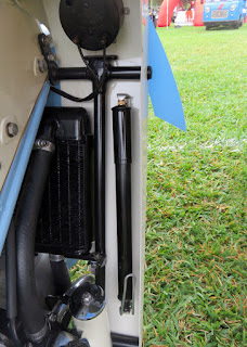 Radiator and air pump are visible inside leg shield of motorcycle.
