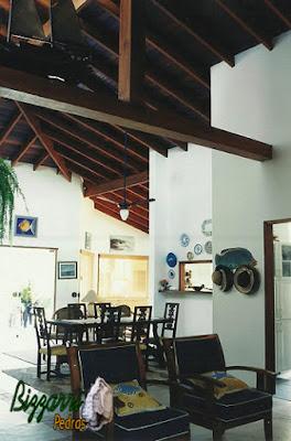 Parte da sala de jantar com o piso de cimento queimado e no madeiramento do telhado o forro por cima dos caibros e na parede a massa desempenada e filtrada de mão única pintado de branco.