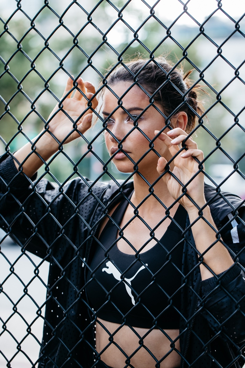 Posing behind the fence, Adriana Lima in PUMA x Maybelline advertisement