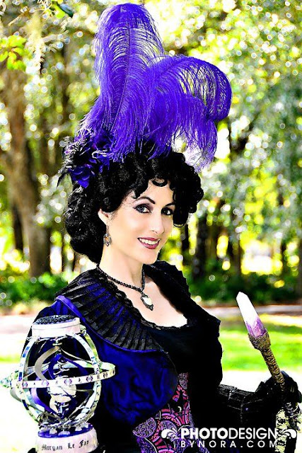 Women's Steampunk comic book cosplay. Purple costume with ostrich plum feather fascinator and peacock feathers, corset and skirt.