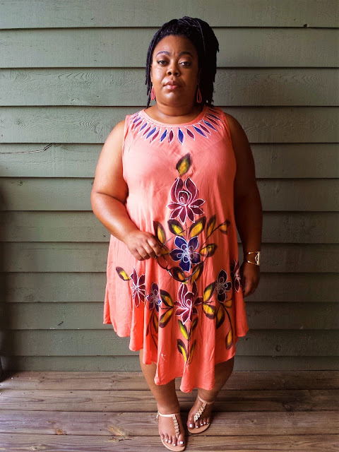 Plus size blogger in sundress, faux locs, light makeup and gold accessories.