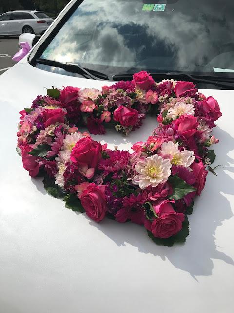 Blütenherz am Brautauto Pink travel themed wedding - Reise ins Glück Hochzeitsmotto im Riessersee Hotel Garmisch-Partenkirchen, Bayern Sommerhochzeit im Seehaus in den Bergen, Hochzeitsplanerin Uschi Glas