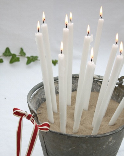 These candles in a bucket of sand are a fun coastal decor piece.