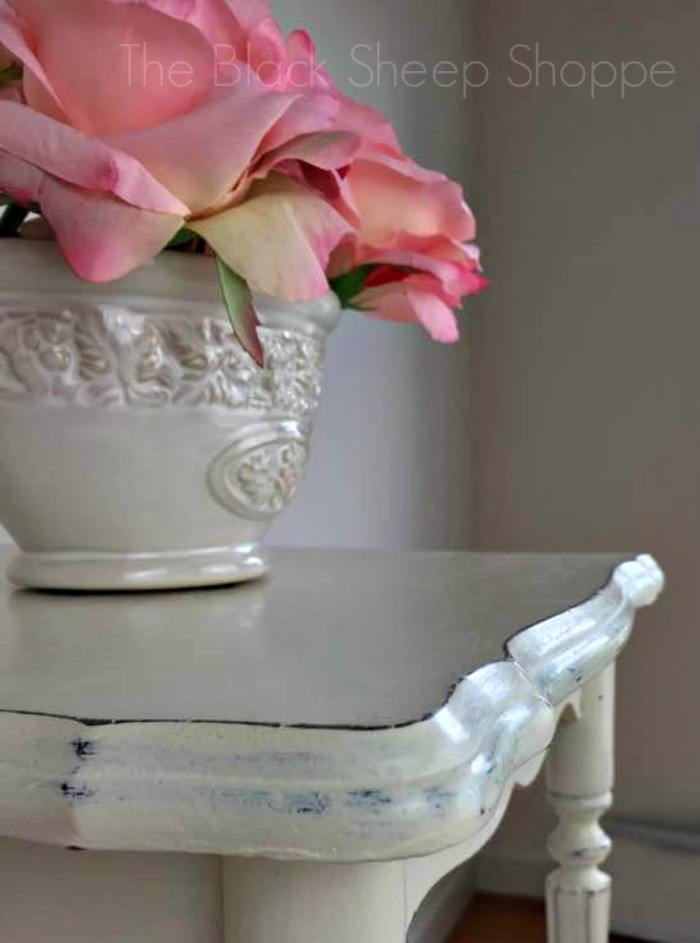 Shabby chic table with vase of pink flowers.