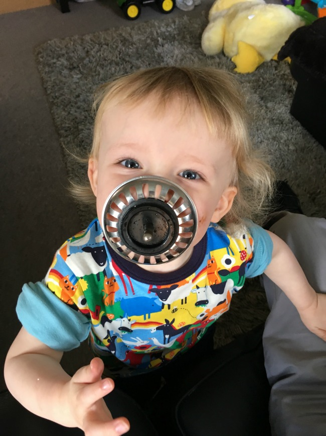 toddler with sink strainer in his mouth