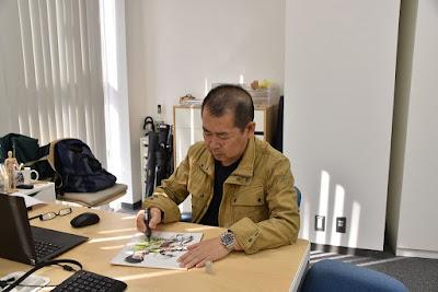 Yu Suzuki signing an illustration