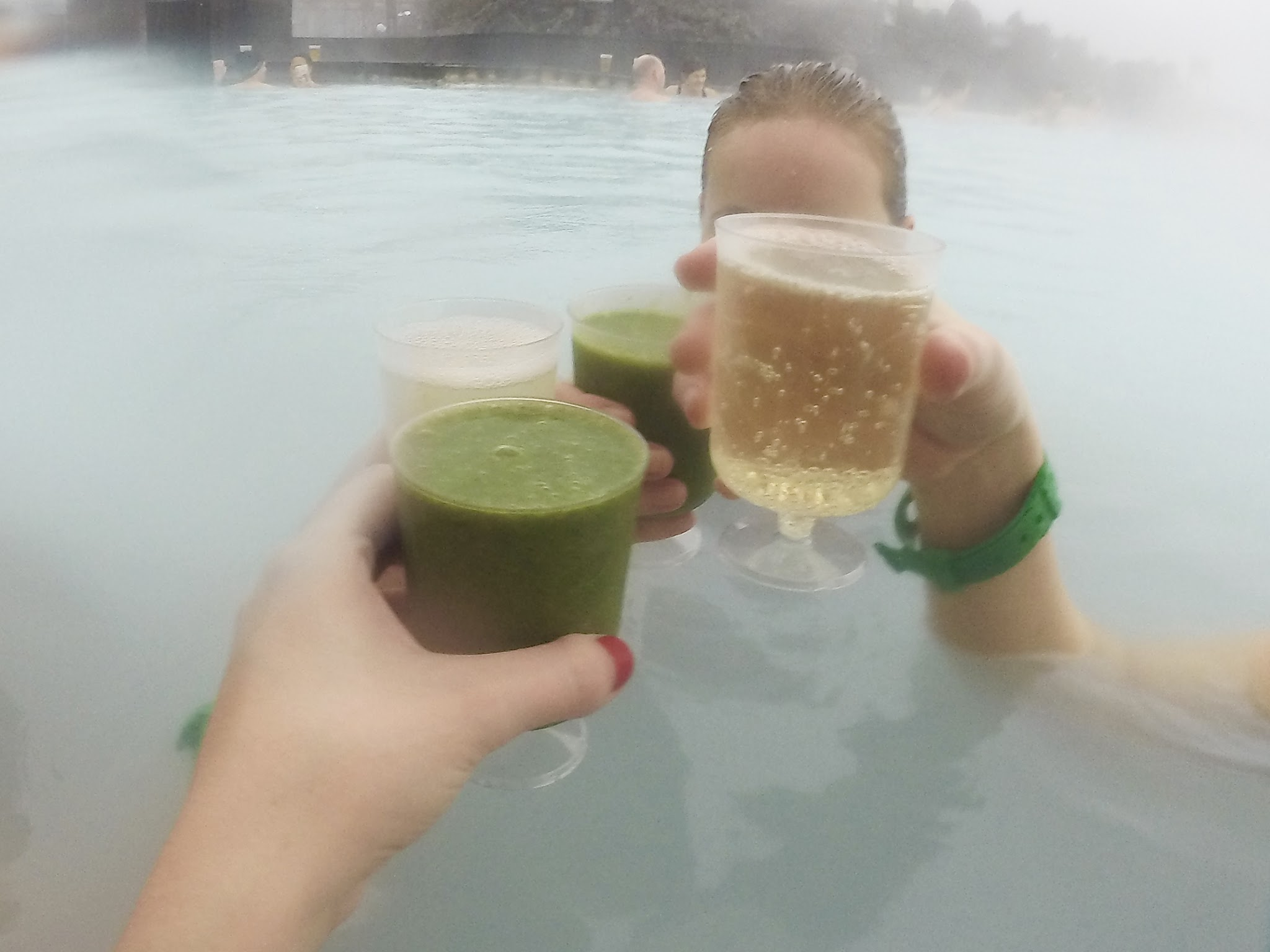 two glasses of prosecco clinking together with two glasses of green juice over the steamy blue water in the lagoon