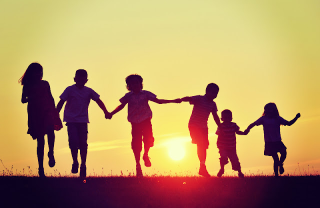 Children running into the sunset holding hands