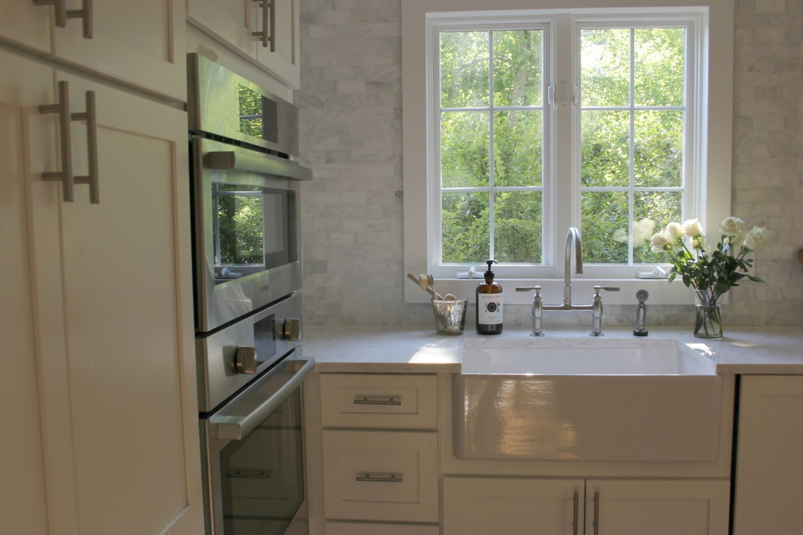 Modern farmhouse kitchen with apron front farm sink and marble subway tile by Hello Lovely Studio