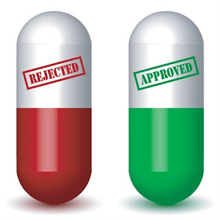 """Two pill capsules, one with the word """"rejected"""" and one with the word """"accepted"""" on them"""