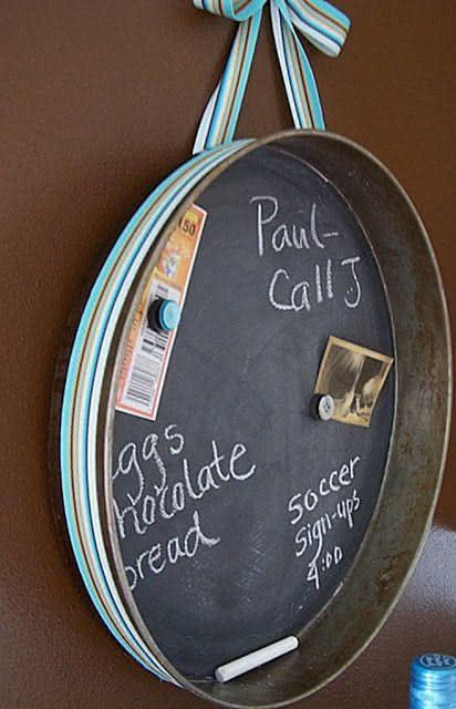 """Uma assadeira que não poderia mais ser usada para cozinhar por estar enferrujada, pode virar um quadro de avisos se usarmos a criatividade. Neste caso o fundo da assadeira foi pintado com tinta lousa e uma fita funciona como """"gancho"""" para que ela fique fixada na parede"""