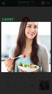 Девушка стоя вилкой ест приготовленный салат из овощей