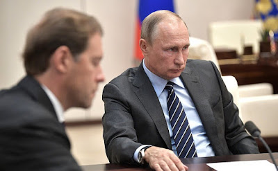 Vladimir Putin with Industry and Trade Minister of Russia Denis Manturov.