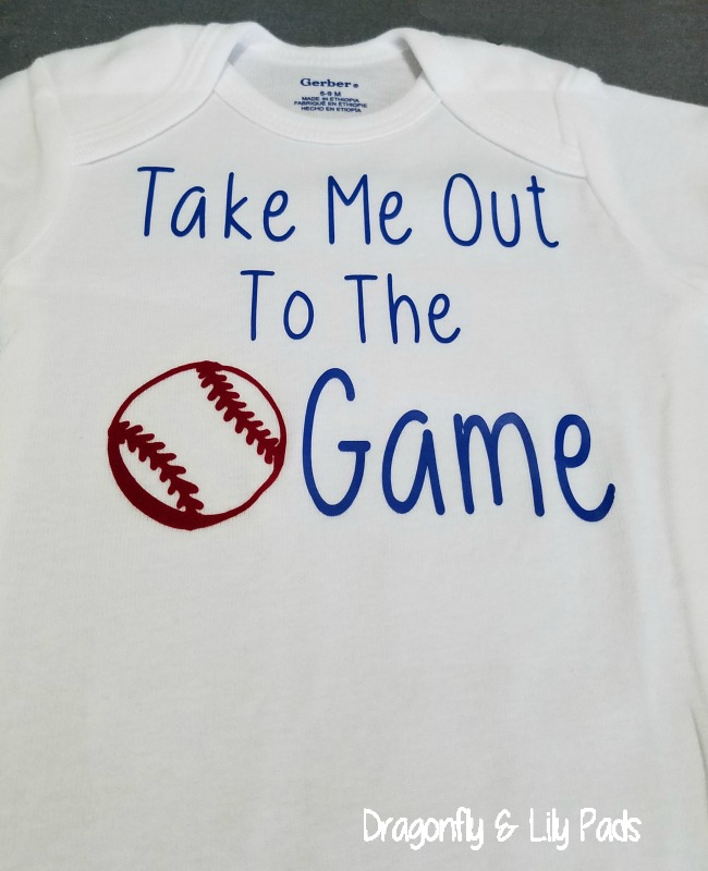 Take Me Out To The Ball Game Onesie made with Cricut Maker. Cricut SportsFlex Deep Blue, A white Gerber Onesie and a Deep Red Flock Iron on.