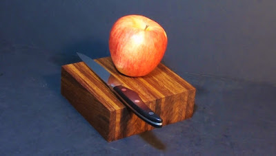 A shiny apple on a cutting board with a knife.