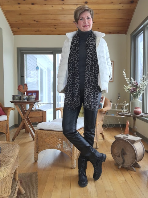 woman in black leather pants, black ankle boots, charcoal turtleneck, black and grey animal print scarf, and white down jacket