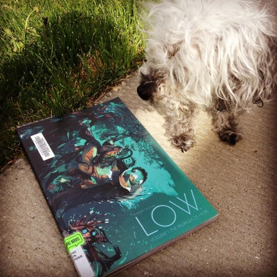Murchie stands on a paved patio, right on the edge of a lawn. Beside him is a trade paperback copy of the first volume of Low. Its blue-toned cover features a woman in a skintight orange diving suit floating upside down against a dark mass.