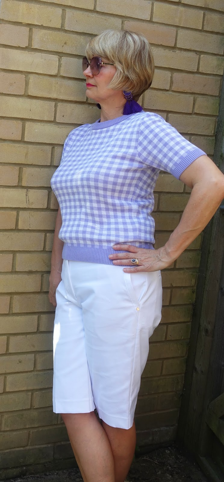 A lilac gingham short sleeved top worn with lilac sunglasses and white knee length shorts by midlife blogger Gail Hanlon from Is This Mutton? dot com