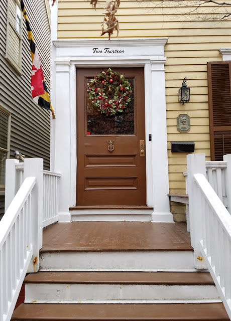 Christmas decor white and brown house with wreath on the door.