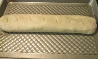 Luego de enrollar el pan de jamón, se procede a pincharlo con un tenedor para que al hornearlo crezca de forma uniforme