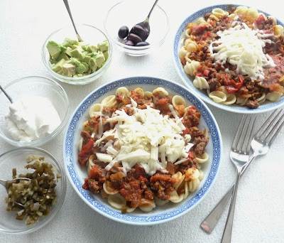 Pasta served with a taco inspired sauce, and taco-style toppings