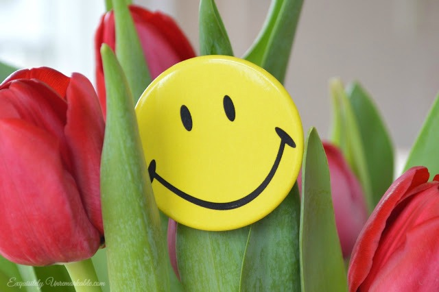 Yellow Smiley Face Button in Vase Of Tulips