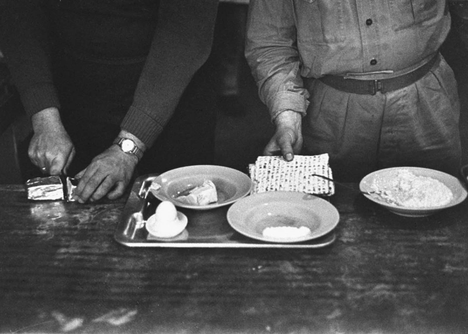 Served by a guard, Eichmann cut breakfast margarine as matzo was put on his tray during Passover week, shortly before trial.