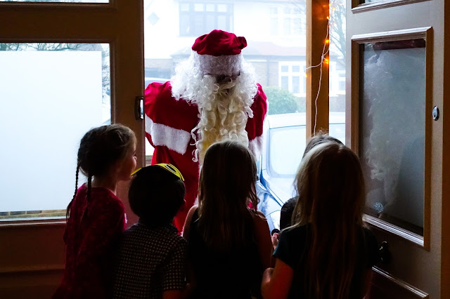 A group of children standing silouetted in a doorway as Father Christmas leans over and talks to them